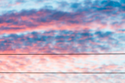 Blue and pink dramatic sunset clouds; 2 parallel telephone wires string across the width of the frame.