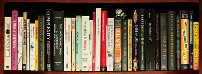A shelf of books, their spines making a poem (described in text). There is a small wind-up robot falling across the tops of the books