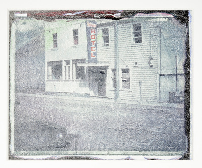 A white clapboard covered building with a blue and red sign that reads Hotel. There is a car parked on the street. Overall the image is grayish and distressed.