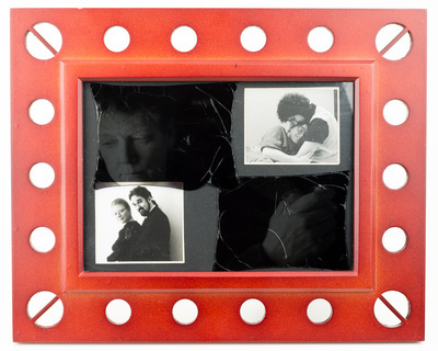 A reddish frame with a dark insert. The insert has two photographs of a couple, one in the upper right (the man and woman are cuddling) and the other in the lower left (the man and woman are posing). In the space between is a dark gray shadow of the woman, looking away from both couple pictures.