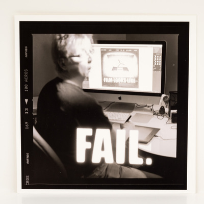 A frame of film, looking at a woman working on a photograph at her computer. She looks surprised. The title is overlaid in white macro text.