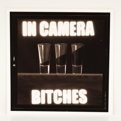 A frame of film, looking at three shot glasses with angled liquid in them. The title is overlaid in white macro text.