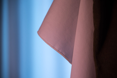 pinkish looking cloth on the left; bluish background; dark stripe on the right