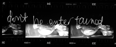 Several frames of 35mm film showing a tabletop setup, handwritten text overlays them which says `don't be entertained`