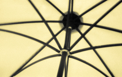 Underside of a market umbrella, with well-defined ribs. The fabric is a pastel yellow and fills the frame.