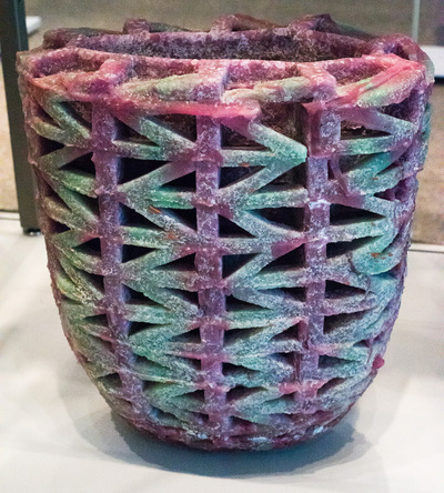 Dusty pink and aqua/green tall bowl/vase with arrow head shapes running horizontally around the length of it.