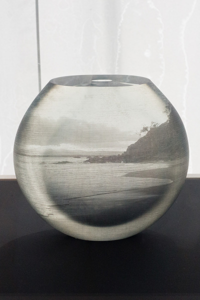 A round vase/bowl with a narrow hole. There is a seascape image on it.