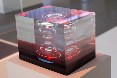 Rectangular cube with layers of red and clear glass. There are concentric circles in the layers.