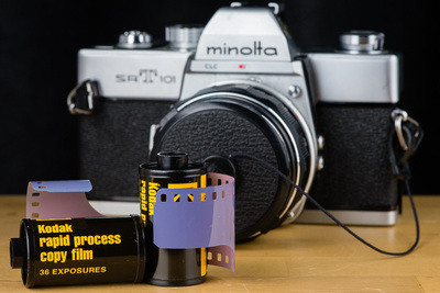 Two film canisters, with tails of purple film hanging out. Behind them is a Minolta SR-T-101 35mm camera.