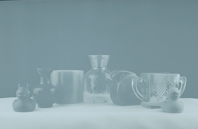 A hazy bluish black-and-white image with several glass items in a row. There is a rubber ducky on each end.