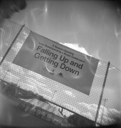 Sign on a chainlink fence, photographed at an angle, reads 'Falling Up and Getting Down'