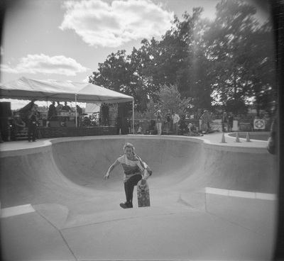 A woman with braided hair is alone in the bowl, her skateboard visible over the edge. A band plays under a canopy.